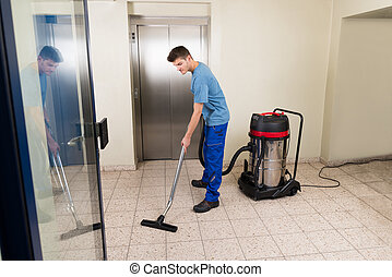 Male Worker Cleaning With Vacuum Cleaner - Happy Male Worker...