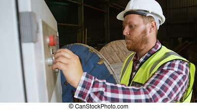 Male worker controlling control box while using digital...