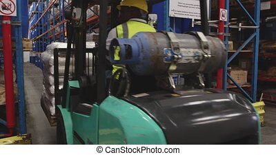 Male worker driving forklift in a warehouse