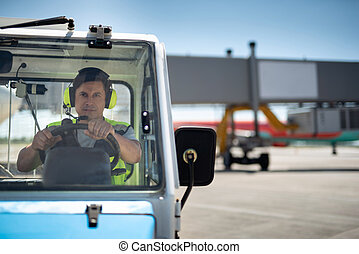 Male worker driving vehicle at airport terminal
