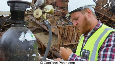 Male worker examining gas cylinder 4k - Male worker...