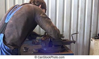 male worker grind rusty metal with rasp tool in garage.