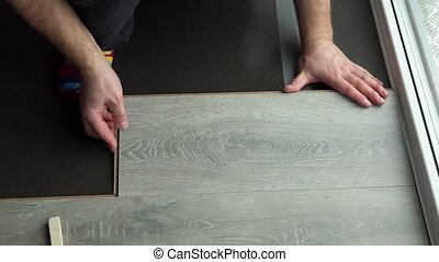 male worker hands lay laminate board floor. Handheld...