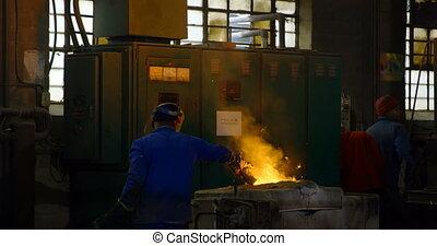 Male worker heating metal in furnace at workshop 4k