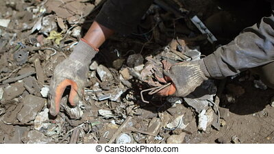 Close-up of male worker holding scraps in the junkyard 4k