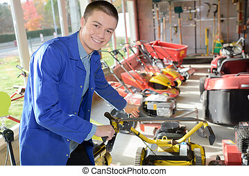 Male worker in lawnmower shop