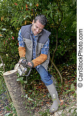 male worker is using a chainsaw