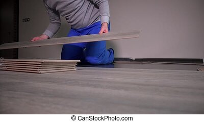 Male worker laminate flooring in new apartment.