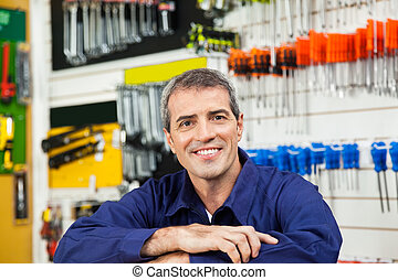 Male Worker Leaning In Hardware Shop