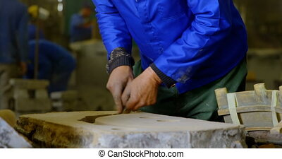 Male worker making metal casting mold in foundry workshop 4k...