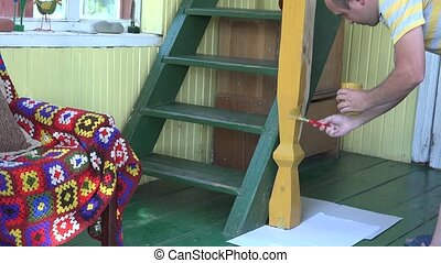 worker man paint wooden column with brush in own home room.