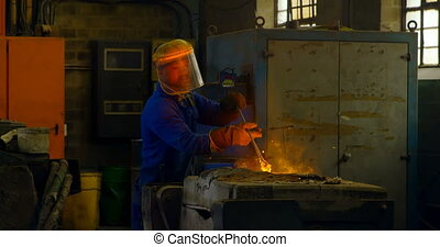 Male worker mixing molted metal in container at workshop 4k