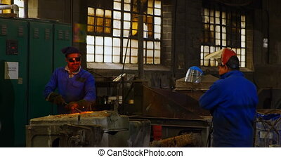 Male worker mixing molted metal in furnace at workshop 4k