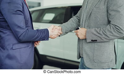 Male worker of car showroom is giving car keys to buyer young man and shking hands with him standing beside luxurious new car. Selling and buying vehicles concept.