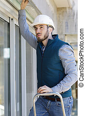 male worker on a ladder outdoors