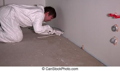 Male worker on knees near electrical wires mounted on wall socket outlet