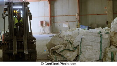 Male worker operating forklift in warehouse 4k - Attentive...