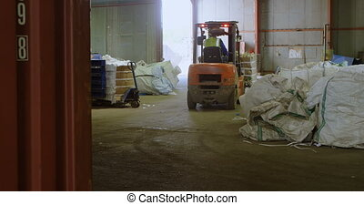 Male worker operating forklift in warehouse 4k - Rear view...