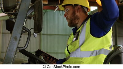 Male worker operating forklift in warehouse 4k - Side view...