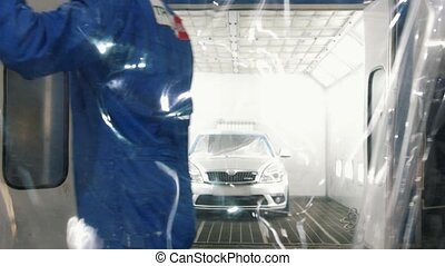 Male worker overlaps room with the car with transparent wrap...