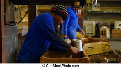 Male worker painting metal casting in workshop 4k - Male ...