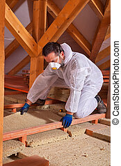 Male worker placing a rock wool thermal insulating panel between the scaffolding of the floor in the attic