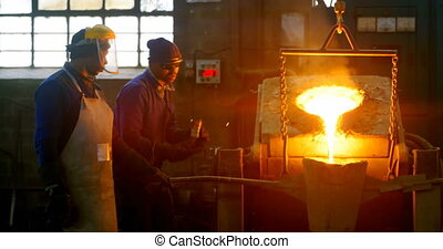 Male worker pouring molten metal in mold at workshop 4k