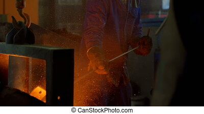 Male worker putting molted metal in furnace at workshop 4k
