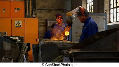 Male worker removing molten metal from furnace in workshop ...