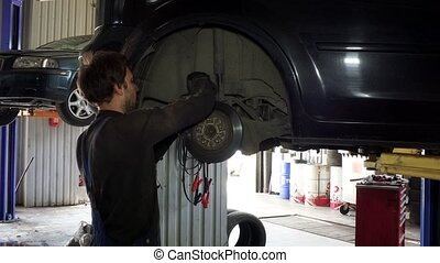 male worker repairing automobile brake system at work.