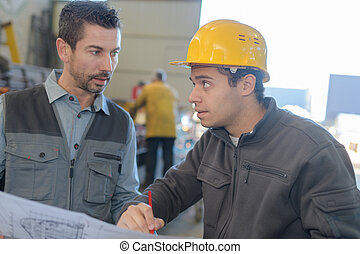 male worker showing something to co-worker at his notebook papers