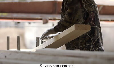 Male worker sorting wooden boards after cutting. Lumber ...