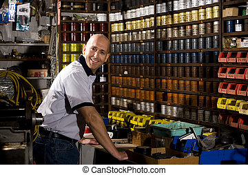 Male worker standing in front of colored inks in print shop