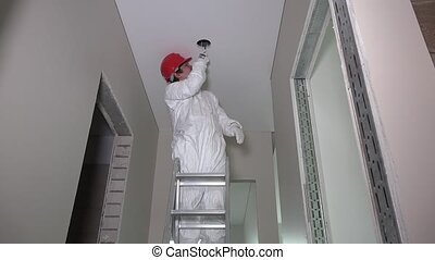 Male worker standing on ladder and cutting hole in corridor ceiling
