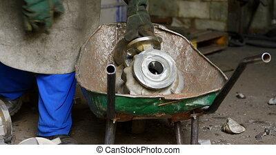 Male worker standing with metal casting in workshop 4k - ...