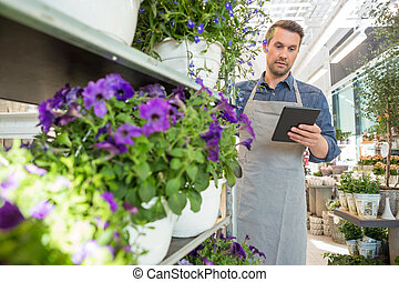 Male Worker Using Digital Tablet In Flower Shop - Mid adult...
