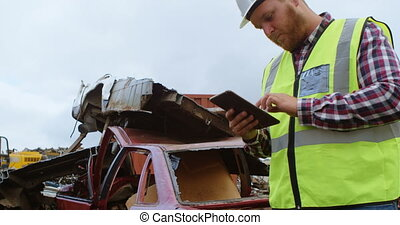 Attentive male worker using digital tablet in the junkyard 4k