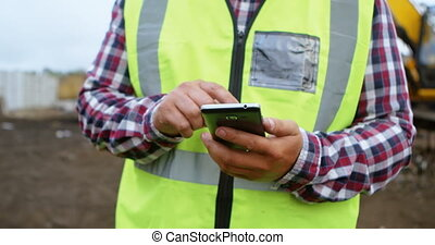 Mid section of male worker using mobile phone in the junkyard 4k