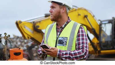 Male worker using mobile phone in the junkyard 4k