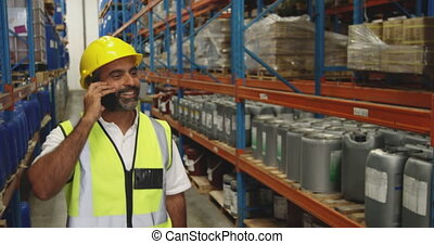 Male worker using smartphone in a warehouse - Side view ...