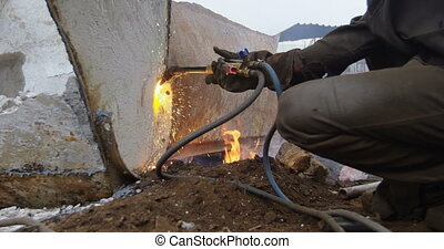 Male worker using welding torch in the junkyard 4k