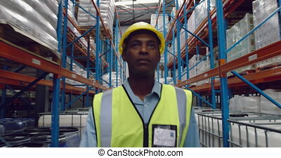 Male worker walking in a warehouse - Front view close up of ...