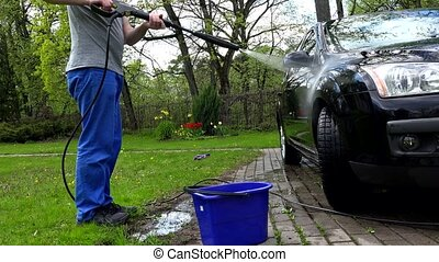 Male worker washing car with power water jet on open air.