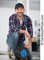 male worker with a reel of electrical extension lead