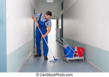 Male Worker With Broom Cleaning Office Corridor - Full ...