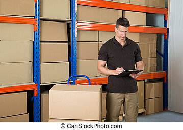 Worker With Cardboard Boxes Writing On Clipboard - Male ...