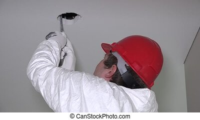Male worker with handsaw cut holes in drywall ceiling for...