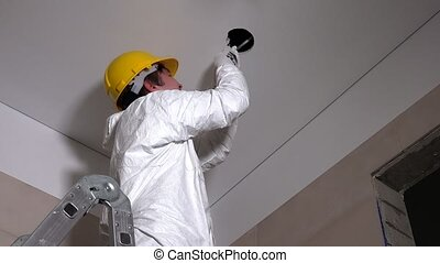 Male worker with helmet cut holes in plasterboard ceiling for light installation