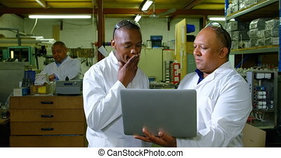 Male workers discussing over a laptop in glass factory. worker working in glass factory 4k