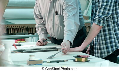 Male workers measuring size of frame behind the desk in workshop